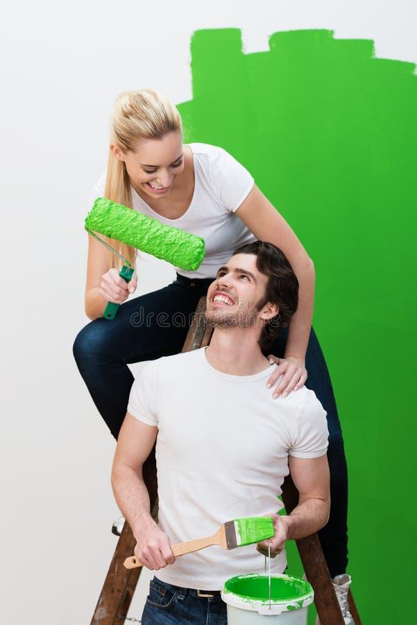 Молодые пары имея потеху по мере того как они красят дом стоковое фото