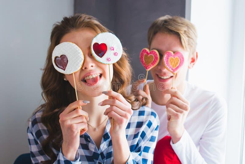 Молодые пары имея потеху совместно, представляющ с леденцами на палочке, девушка показывая язык стоковая фотография rf