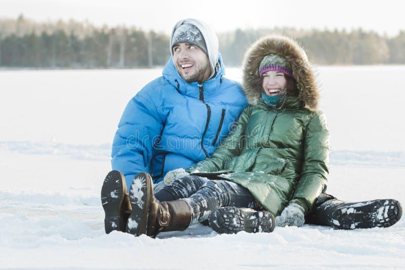Молодые пары имея потеху outdoors сидя на снежном земном заволакивании во время вьюги зимы стоковые изображения rf