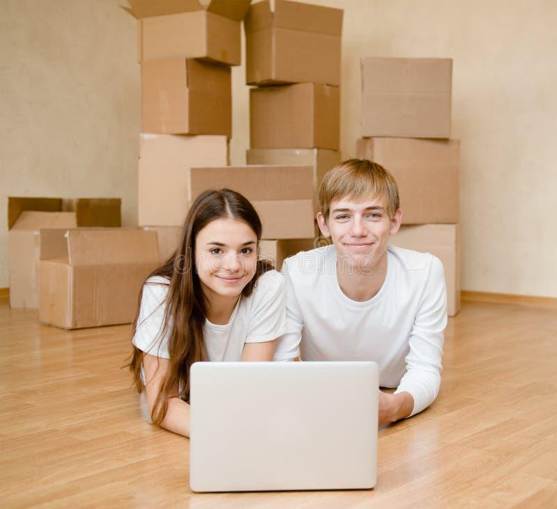 Молодые пары используя компьтер-книжку в их новом доме стоковые фото