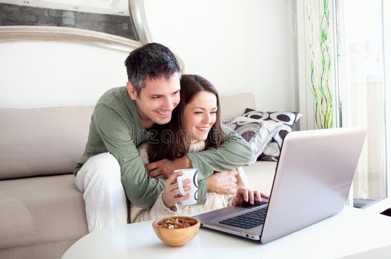 Молодые пары используя компьтер-книжку стоковое фото