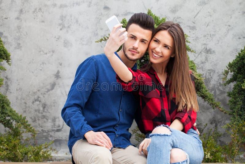 Молодые пары используя умный телефон стоковые фотографии rf