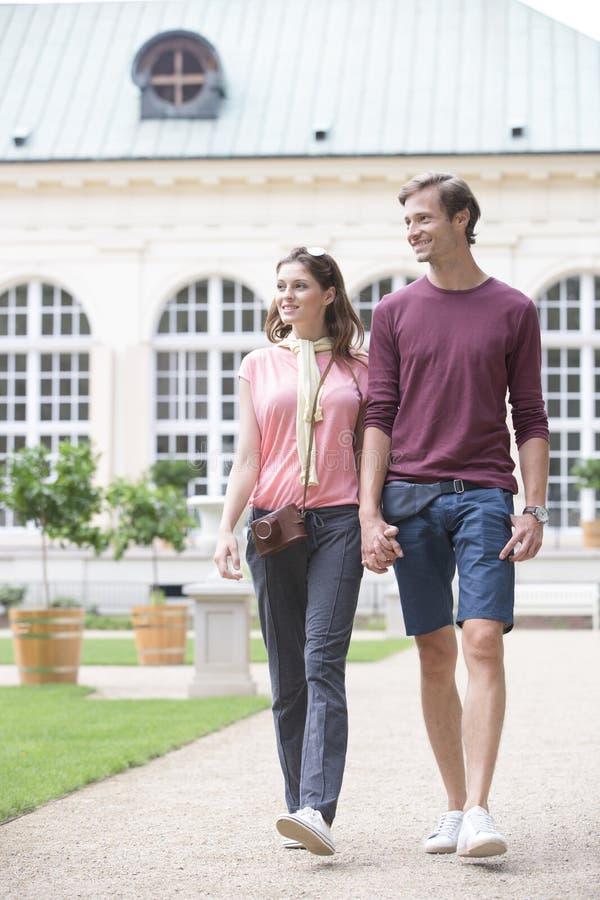 Молодые пары идя против зданий стоковые фото