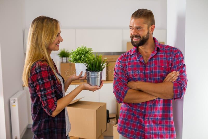 Молодые пары как раз двигают к их новой квартире Они говорят стоковые фото