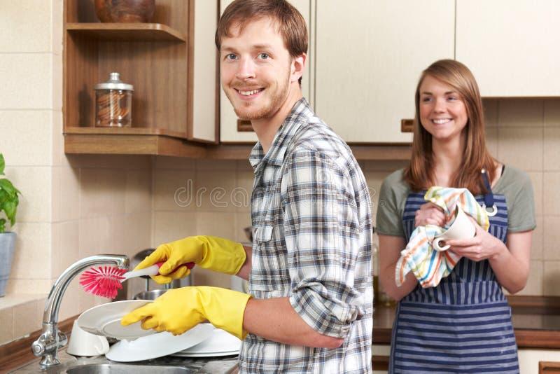 Молодые пары моя вверх на раковине совместно стоковая фотография rf