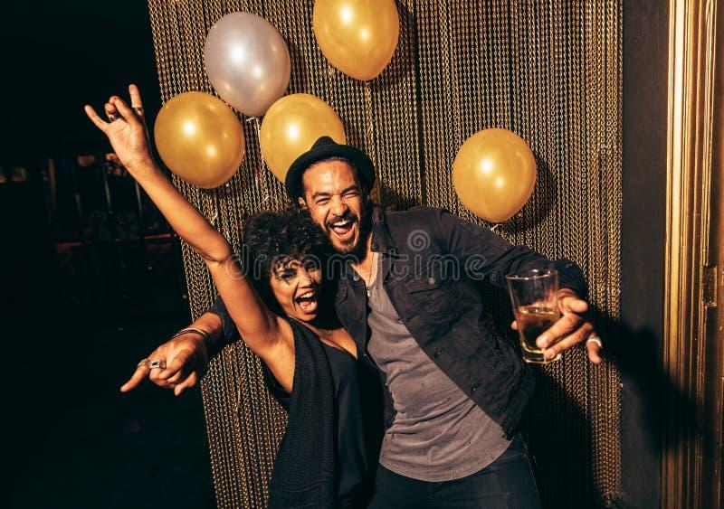 Молодые пары наслаждаясь партией на клубе стоковое фото