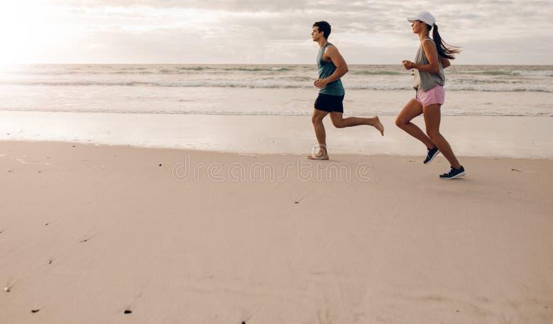 Молодые пары на бежать вдоль берега стоковая фотография