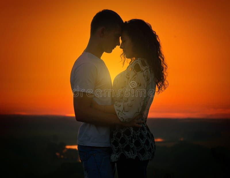 Молодые пары на заходе солнца на предпосылке неба, концепции влюбленности, романтичных людях стоковая фотография
