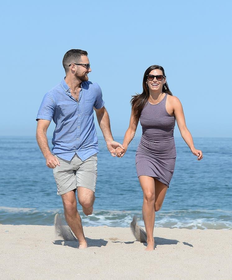 Молодые пары на песчаном пляже стоковые изображения rf