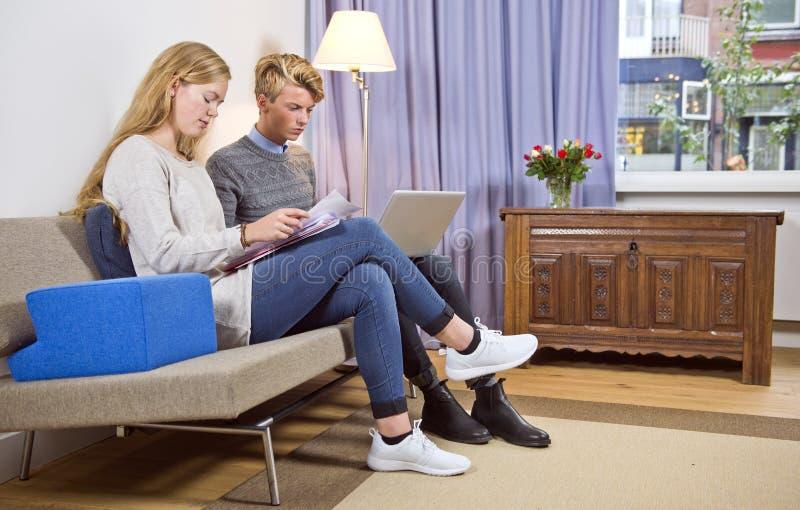 Молодые пары на софе делая их личную администрацию стоковые изображения rf