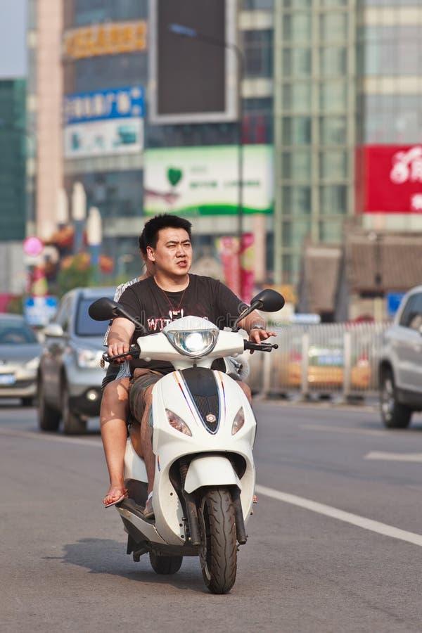 Молодые пары на электрическом самокате, Пекине, Китае стоковое изображение