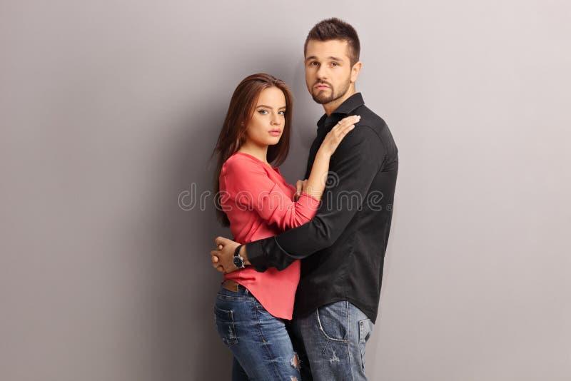 Молодые пары обнимая против серой стены стоковое изображение