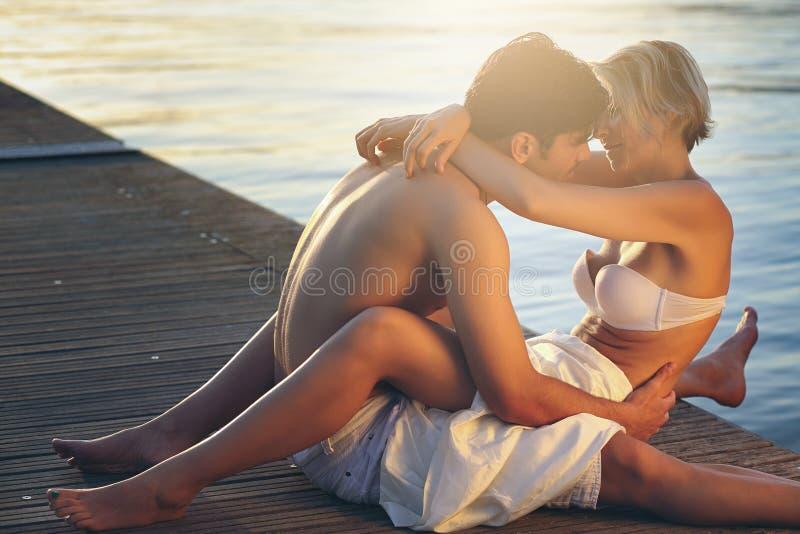 Молодые пары обнятые на пристани моря стоковое изображение rf