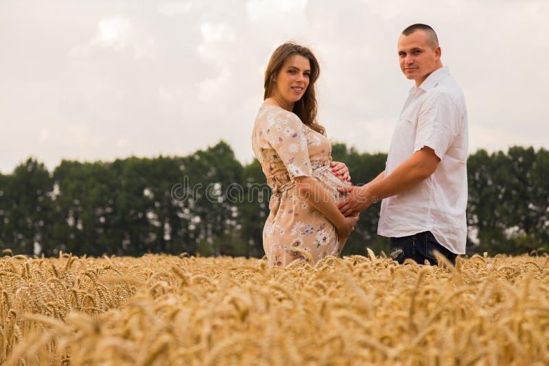 Молодые пары ожидая младенца среди пшеничного поля стоковые фото