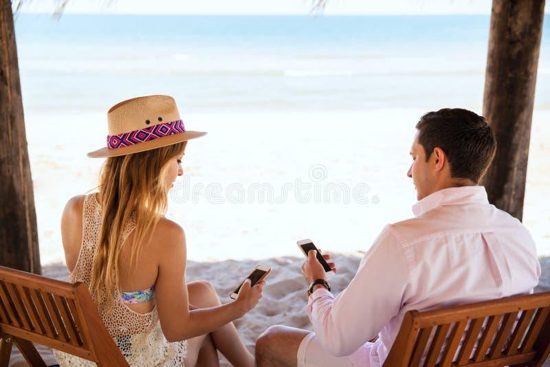 Молодые пары отвлеченные технологией стоковая фотография rf