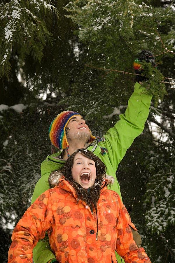 Молодые пары под снежным деревом стоковая фотография