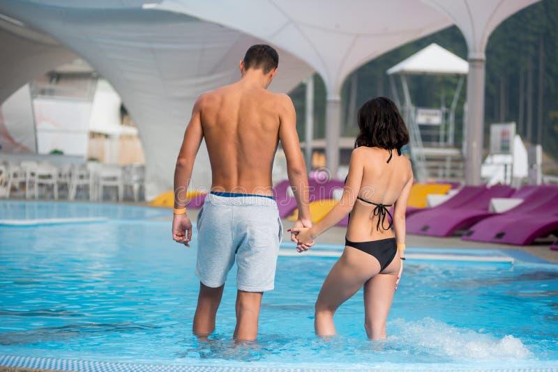 Молодые пары при совершенная диаграмма стоя в бассейне и держа руки на роскошном курорте задний взгляд стоковая фотография rf