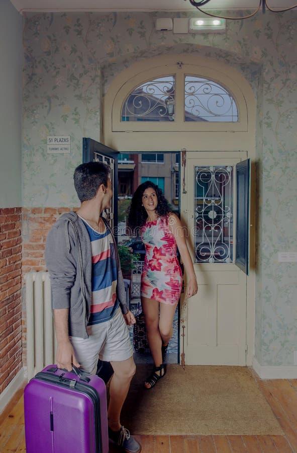 Молодые пары при чемоданы приезжая к общежитию стоковое изображение
