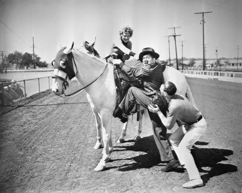 Молодые пары пробуя помочь человеку получить на его лошадь (все показанные люди более длинные живущие и никакое имущество не суще стоковые фотографии rf