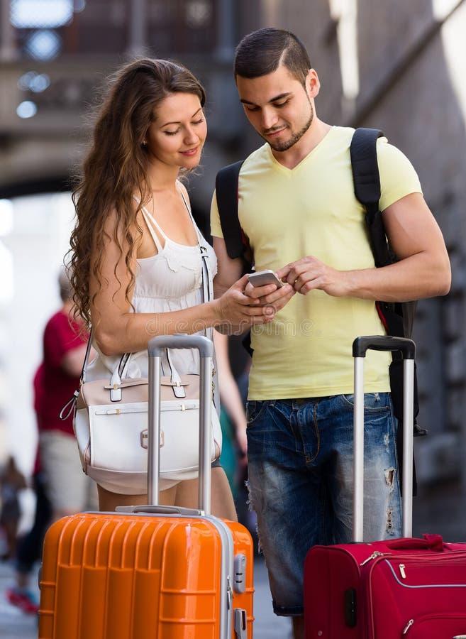 Молодые пары путешественников находя путь с телефоном стоковая фотография