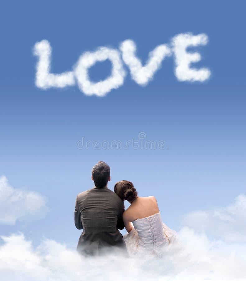 Молодые пары сидя на облаках стоковое изображение rf