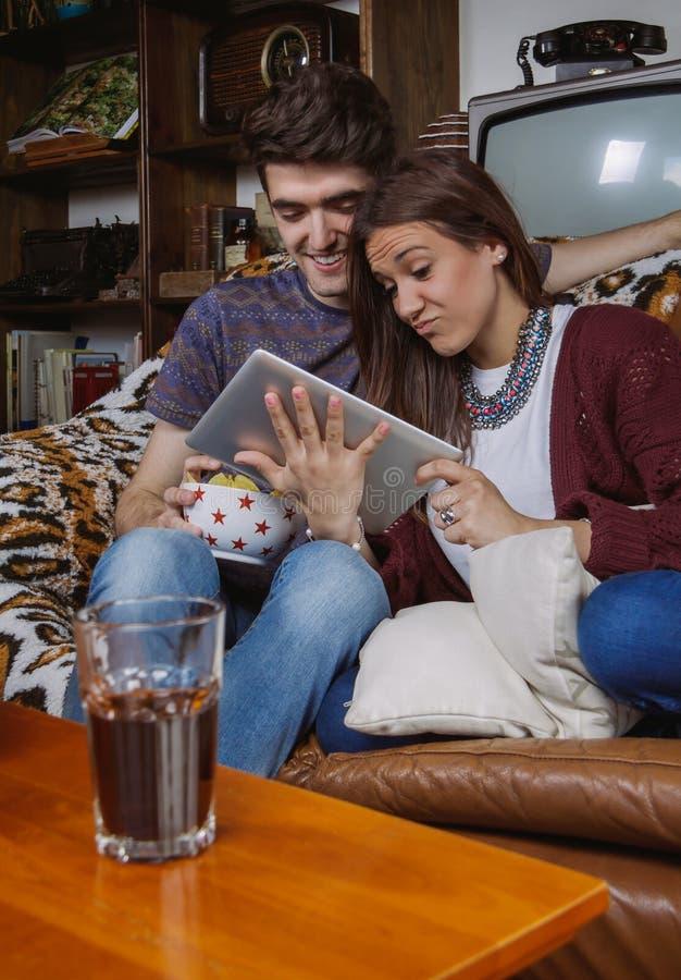 Молодые пары смеясь над и смотря усаживанием таблетки стоковое изображение