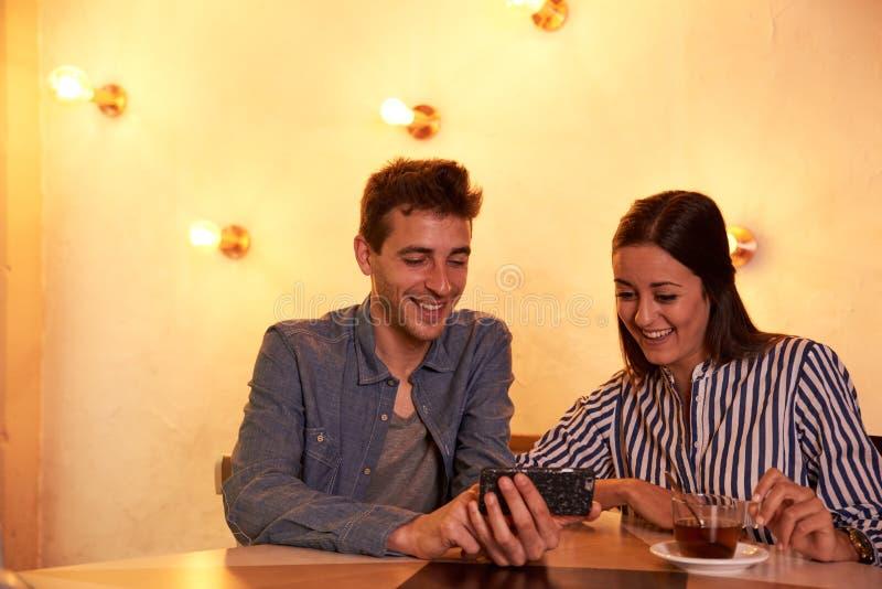 Молодые пары смеясь над на изображениях мобильного телефона стоковые фотографии rf