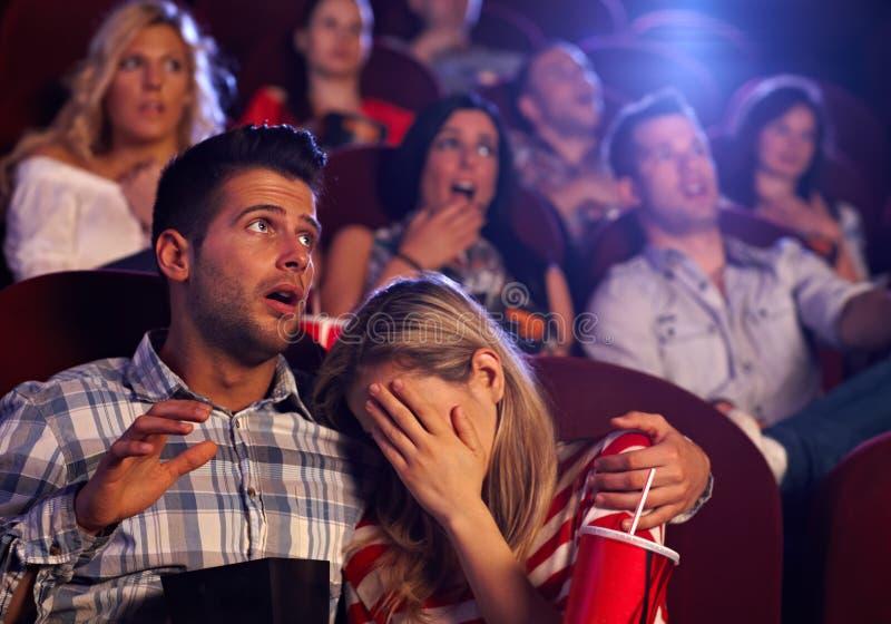 Молодые пары смотря ужас в кинотеатре стоковое фото