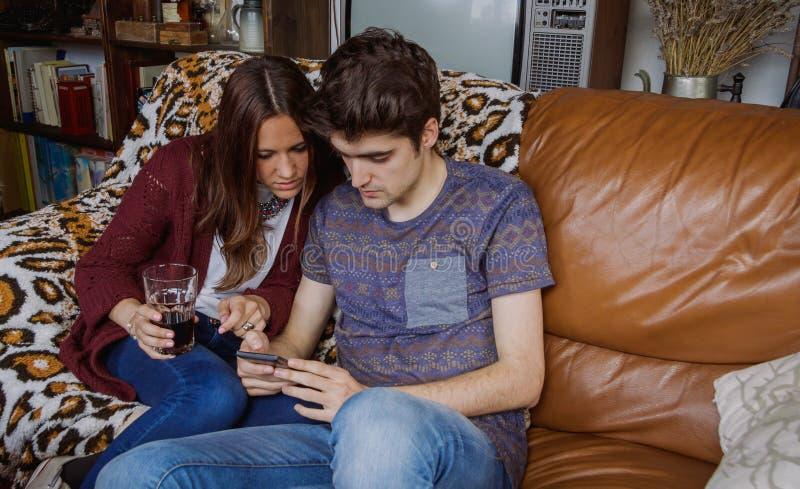 Молодые пары смотря smartphone сидя на софе стоковые изображения