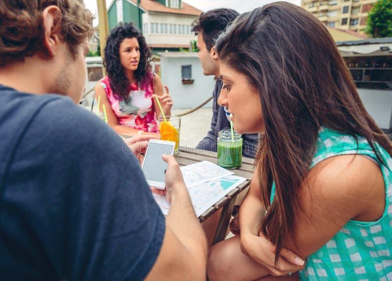Молодые пары смотря smartphone outdoors в лете стоковое фото
