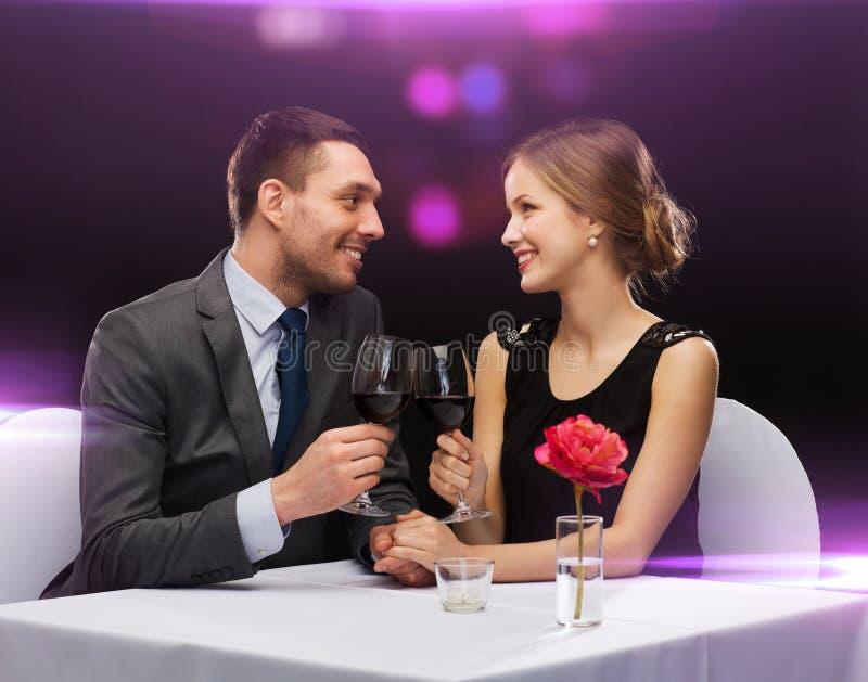 Молодые пары с стеклами вина на ресторане стоковое изображение