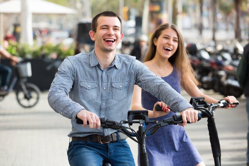 Молодые пары с электрическими велосипедами стоковые изображения