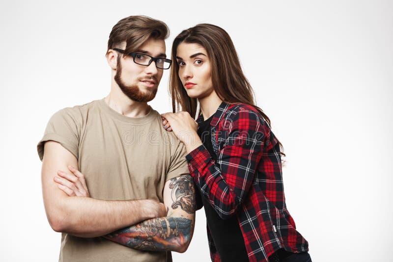 Молодые пары хмурясь на камере, смотря сотрясенный Изолировано на белизне стоковое фото