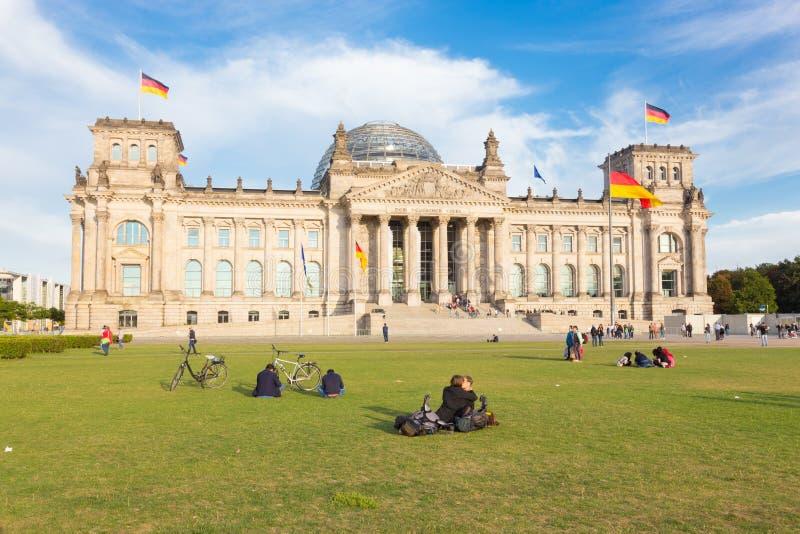 Молодые пары целуя на луге перед зданием Reichstag в Берлине, Германии стоковое изображение