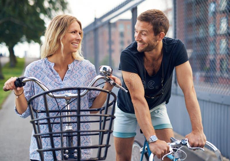 Молодые пары flirting по мере того как они беседуют в улице стоковое изображение