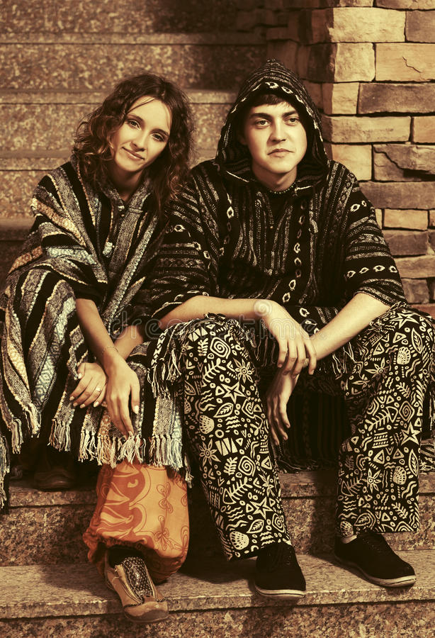 Молодые пары hippie моды сидя на шагах стоковое изображение rf