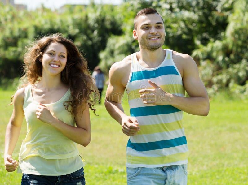 Молодые пары joggers делая бежать на парке стоковое фото