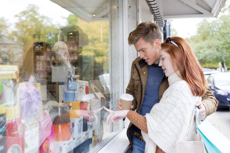 Молодые покупки окна пар стоковое изображение