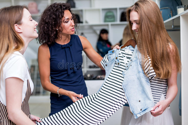 Молодые подруги выбирая новые одежды совместно держа, оценивающ, обсуждающ платье в магазине одежды стоковые изображения