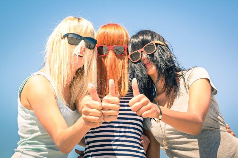 Молодые подруги с смешными волосами имеют потеху с большими пальцами руки вверх стоковая фотография