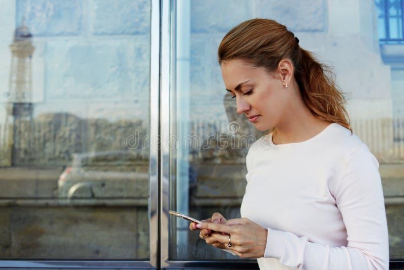 Молодые привлекательные данные по чтения женщины через сеть на мобильном телефоне пока ждущ автомобиль на станции, стоковая фотография