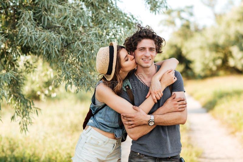 Молодые привлекательные пары битника целуя на предпосылке леса стоковое фото