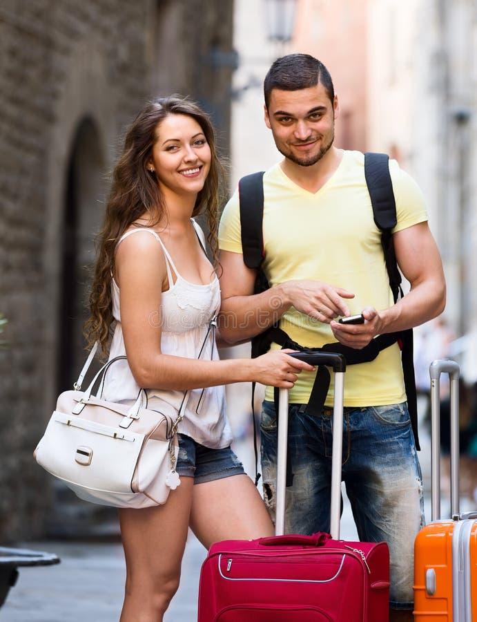 Молодые путешественники находя путь с телефоном стоковое фото