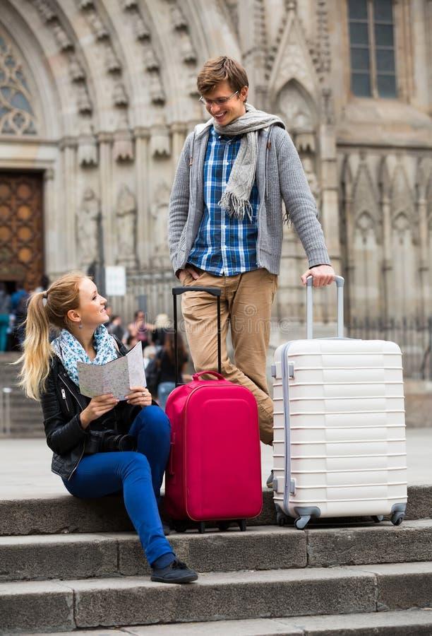 Молодые путешественники с картой города на улице стоковые фото