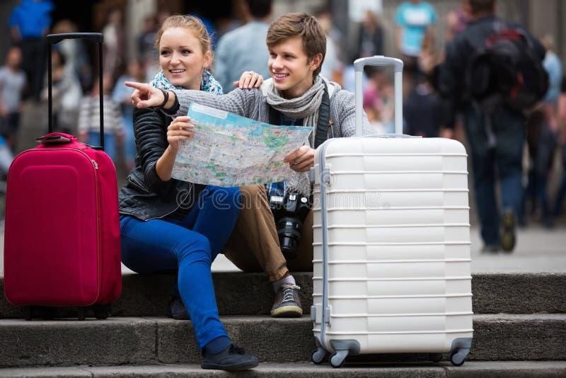 Молодые путешественники с картой города на улице стоковые изображения