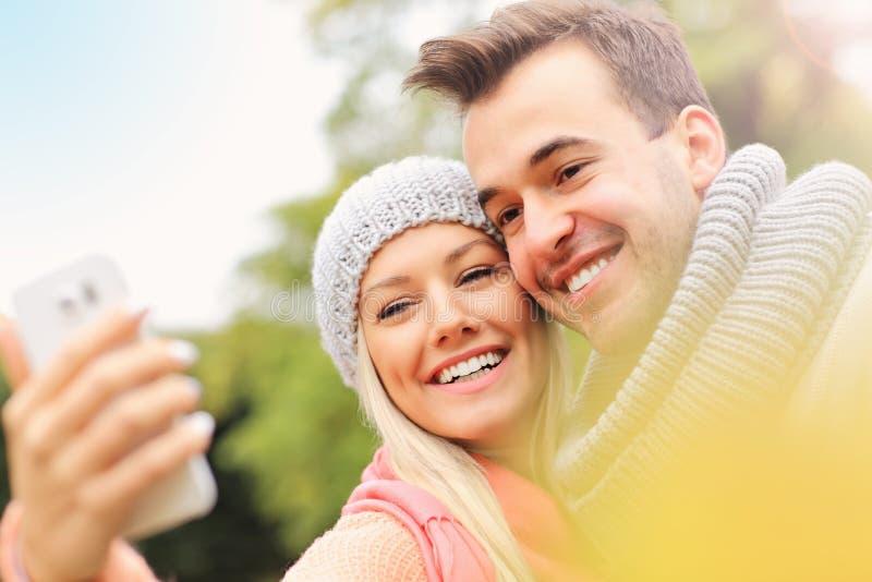 Молодые романтичные пары принимая selfie в парке в осени стоковые изображения rf