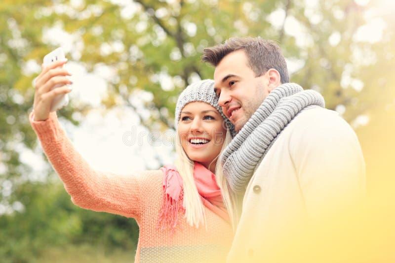 Молодые романтичные пары с smartphone в парке в осени стоковая фотография