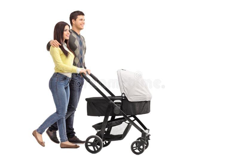 Молодые родители нажимая детскую сидячую коляску стоковые фото