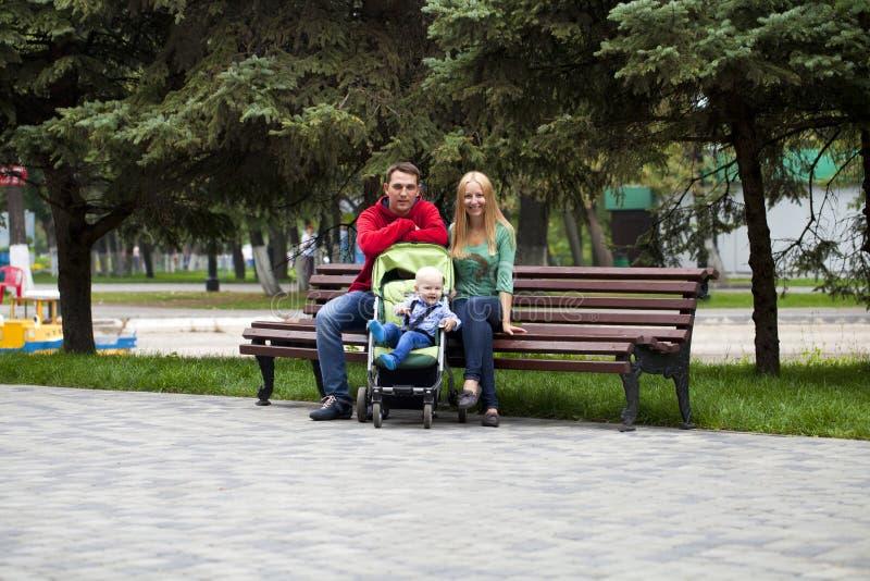 Молодые родители сидят на стенде с его молодым сыном стоковое фото