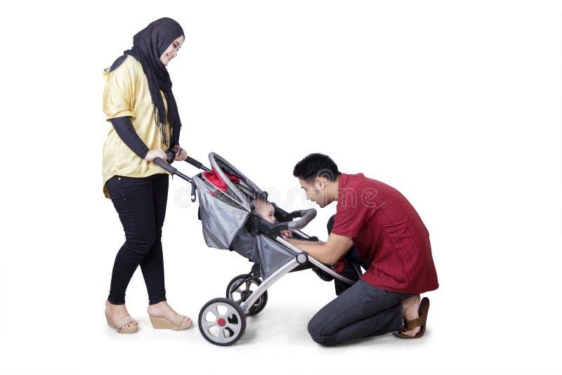 Молодые родители с младенцем на прогулочной коляске стоковое фото rf